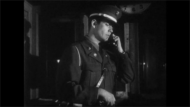 1950s: UNITED STATES: guard at gate. Man answers telephone. Soldier puts down phone