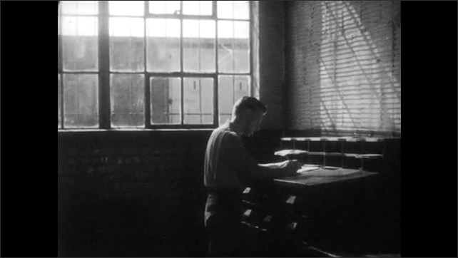 1950s: UNITED STATES: soldiers stand together. Boxes behind cage bars. Man writes in office. Soldiers work at desks.