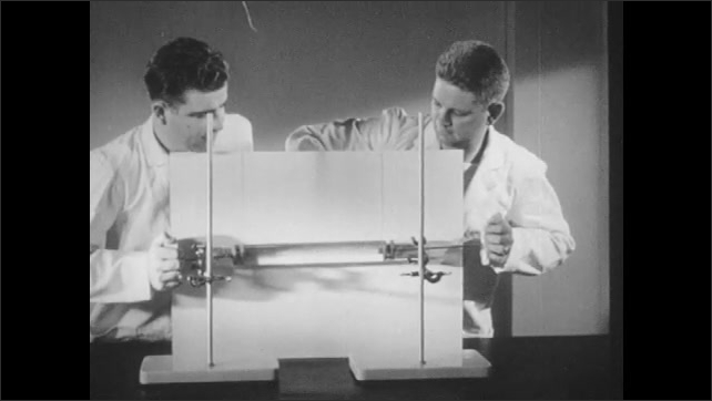 1940s: Men in lab coats apply equal force to pistons inside test tube of water from either end of tube. Man in lab coat pushes pistons on either end of glass test tube full of water.