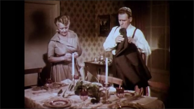 1950s: Dining room.  Husband and wife speak.  Woman lights candle.