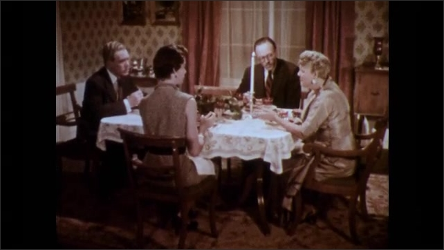 1950s: Dinner party.  Woman returns to table.  People sit and eat.  Young man talks on telephone.  People talk.