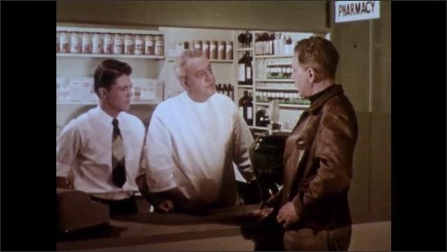 1950s: Man stands at pharmacy window.  Men speak.  Men shake hands.