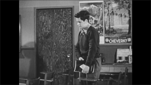 1950s: Teacher and teenage boy sit.  Boy stands and walks to desk.  Boy picks up books and speaks.  Boy leaves classroom and shuts door.