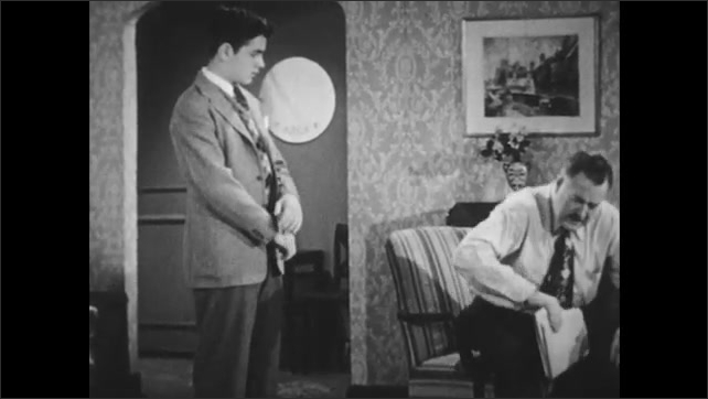 1950s: Teenage boy fastens tie in mirror.  Boy walks into living room.  Father and boy speak.  Man stands and moves to desk.  Men sit.