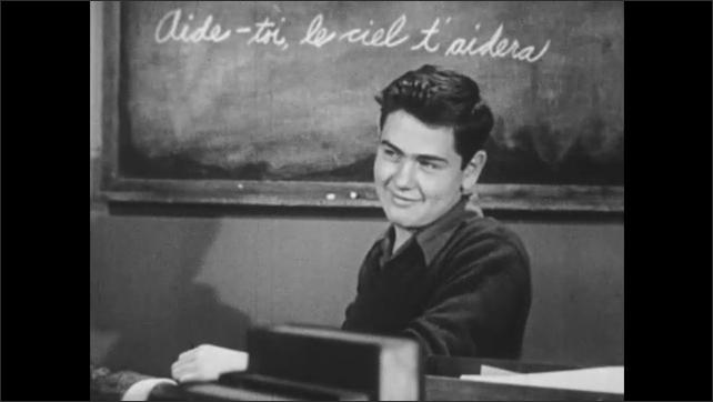 1950s: Man sits at desk and speaks.  Man turns to teenage boy.  Boy smiles.