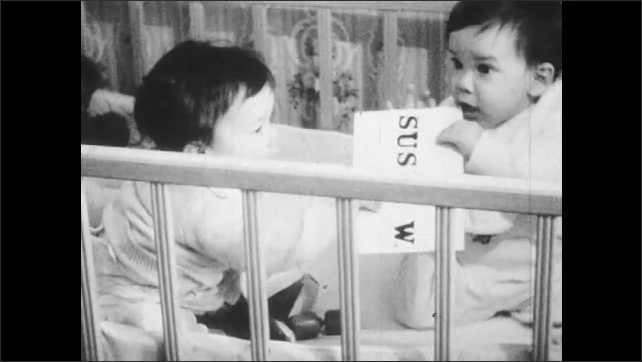 1960s: Two babies in a crib play with a piece of paper.