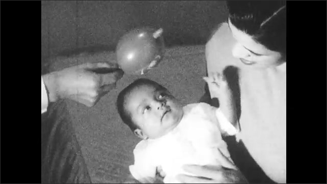 1960s: Woman holds baby, baby looks at woman. Man shakes toy near baby.