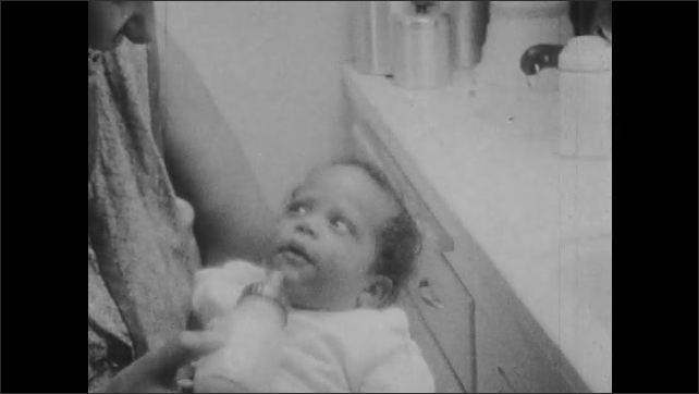 1960s: Woman holds baby, feeds baby a bottle, talks to baby. Baby looks at woman.