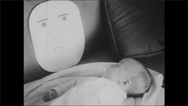 1960s: Baby lays on couch, person holds a drawing of a frowny face in front of baby, baby looks at drawing. Person holds blank paper in front of baby, moves paper around, baby ignores paper.