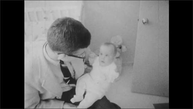 1960s: Woman sits with baby on lap, plays with baby. Man sits with baby on lap, bounces baby.