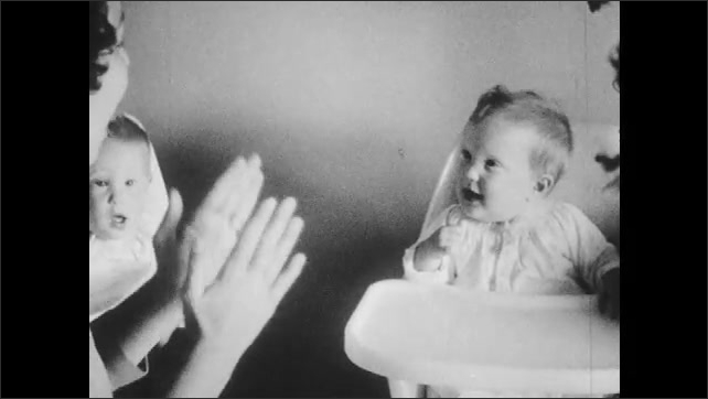 1960s: Babies sit in highchairs, woman talks to baby, claps hands, baby smiles.