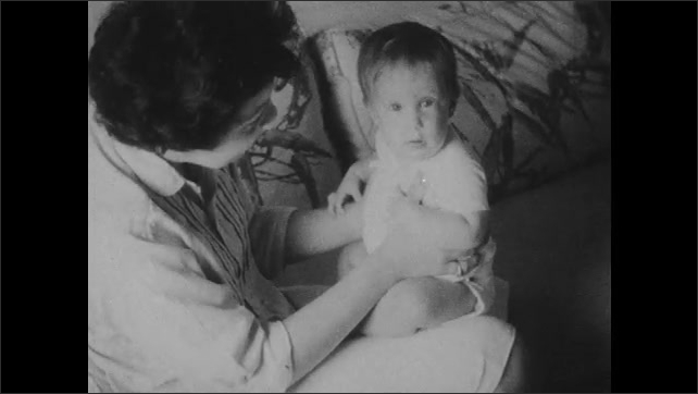 1960s: Sign with baby's name and age. Woman sits on couch with baby, talks to baby, plays with baby.
