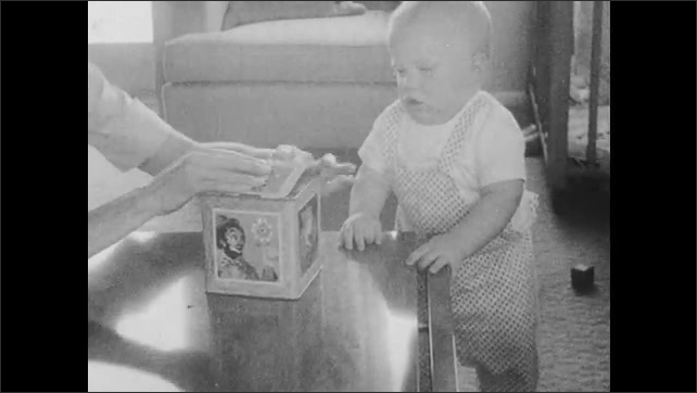 1960s: Baby stands next to coffee table, woman winds jack in the box next to baby, jack pops out of box, baby looks at toy. Woman winds toy again.
