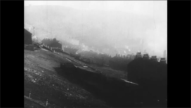 1950s: UNITED STATES: fire in furnace. Wheel spins. Industrial town with chimneys and smoke.