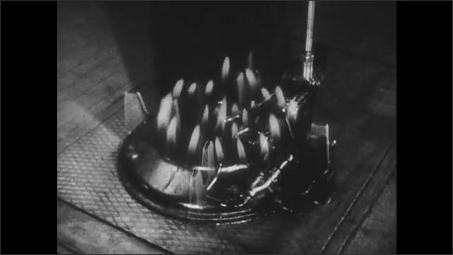 1950s: UNITED STATES: miners mine for coal. Gas lit flame. Wheels on engine