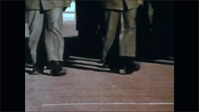 1960s: UNITED STATES: cadets march during drill practice. Man looks at camera