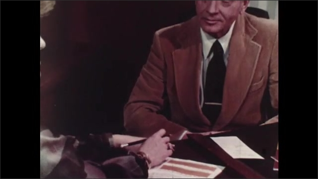 1980s: Two women and three men stand shoulder to shoulder, each holding a piece of paper. Man sits across desk from woman, talking.