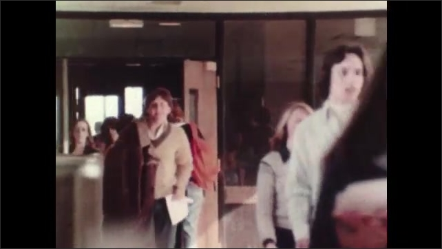 1980s: Students walk through hallway of school.