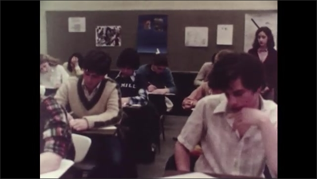 1980s: Students at desks in classroom, taking tests. Students in classroom take tests at desks while person walk around room monitoring them. Students take tests at desks.
