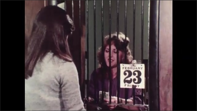 1980s: Woman sits at desk, across from man, talking while looking at paper laying on desk. Cashier behind bars counts out money for woman waiting at window. Woman types on computer.