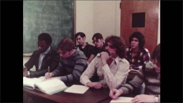 1980s: Students sit at desks in classroom. Man and woman sit at desk with books and pencils.