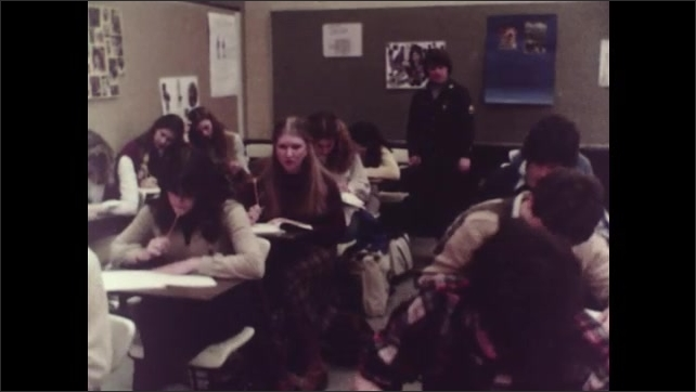 1980s: Students at desks in classroom, taking tests while person stands in room monitoring them. Posters on wall advertising the military.