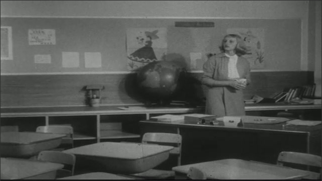 UNITED STATES 1950s: Woman in classroom, cleans desk / Teacher talks with students / Woman cleans desk.
