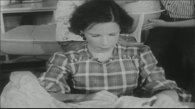 UNITED STATES 1950s: Girl at desk, takes food from bag, eats sandwich