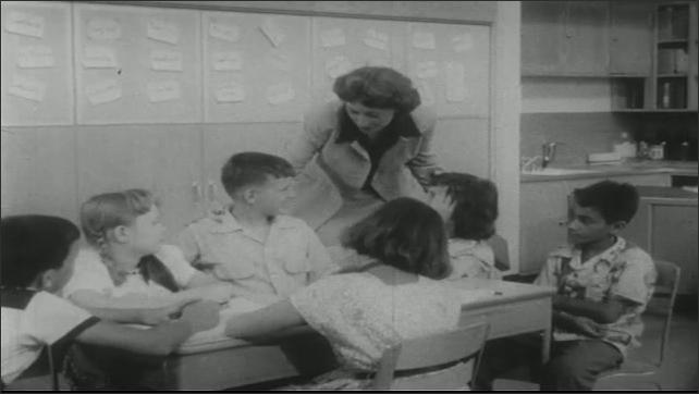 UNITED STATES 1950s: Close up of boy / Kids in classroom, teacher approaches kids / Boy sulking / Close up, boy nods.
