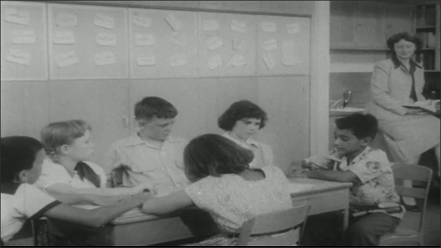 UNITED STATES 1950s: Close up of teacher / Kids in classroom / Close up of boy.
