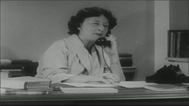 UNITED STATES 1950s: Woman talks on phone at desk.