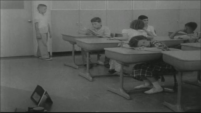 UNITED STATES 1950s: Boy in classroom / Teacher at desk / Girl seated at desk talks / Panning shot, boy walks to desk.