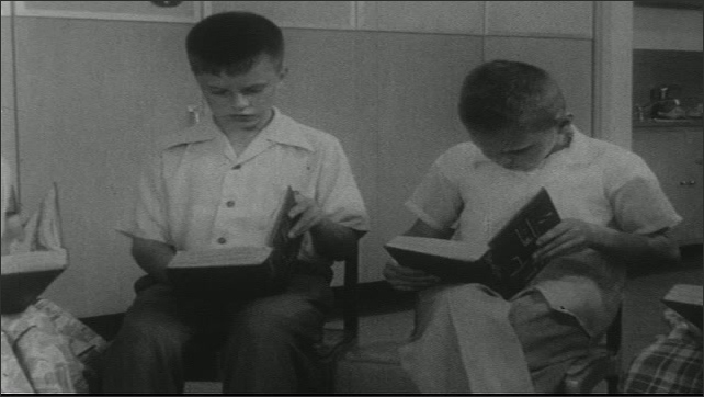 UNITED STATES 1950s: Close up of boy / Boys read in group / Boy catches ball, boy stands in background.