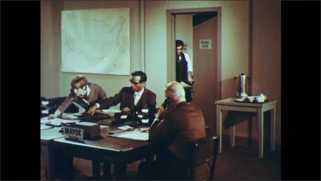 1960s: UNITED STATES: civil defense operating centre. Man enters office. Workers in office