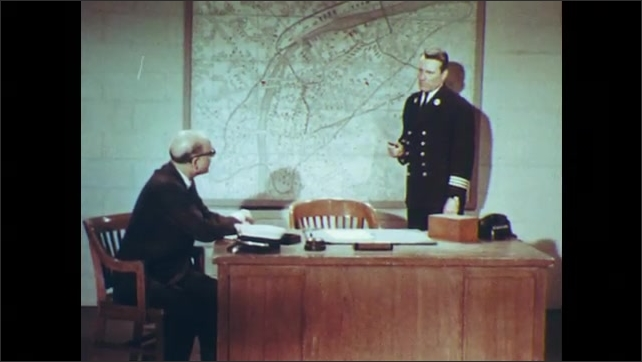 1960s: UNITED STATES: fire engine at fire station. Man walks past fire engine. Man meets with fire inspector. Man sits at desk