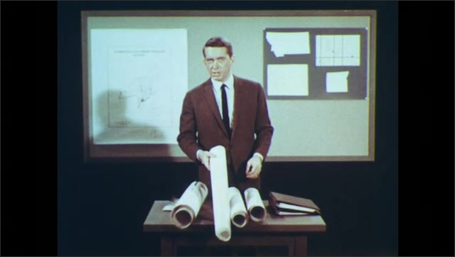 1960s: UNITED STATES: man stands in front of monitor. Papers rolled up. Man shows rolled paper to camera. Man speaks to camera