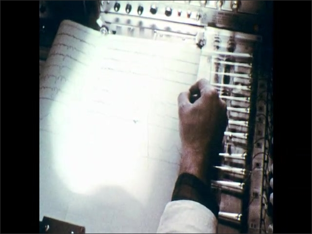 1970s: Arm of man with wires and monitors attached. Hand with pen marks line charts on monitor. City streets and buildings of Lexington, Kentucky.