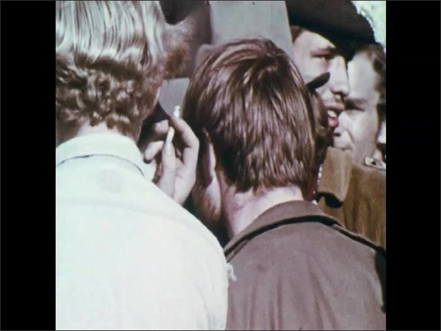 1970s: Homeless man on doorstep. Drugs on shelves of pharmacy. City ghetto. Young people chant and protest. Police light spins. Police in riot gear march down sidewalk.