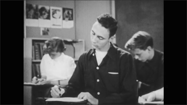 1950s: Boy seated at desk in classroom takes test. Highlighted question on test. Boy writes on paper at desk.