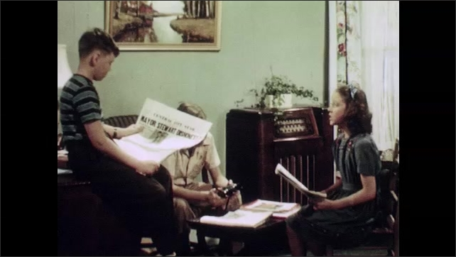 1950s: UNITED STATES: boy stands with broken bike chain. Children read advert in newspaper
