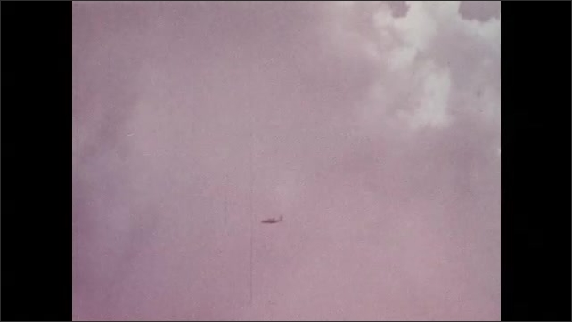 1970s: Plane flies through clouds.