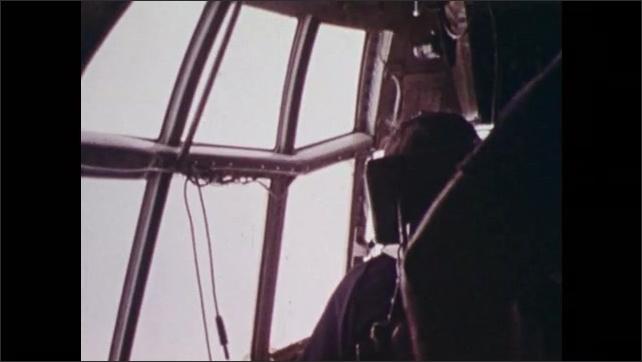1970s: Man gestures in airplane cockpit.  Plane flies through clouds.  Man presses button.