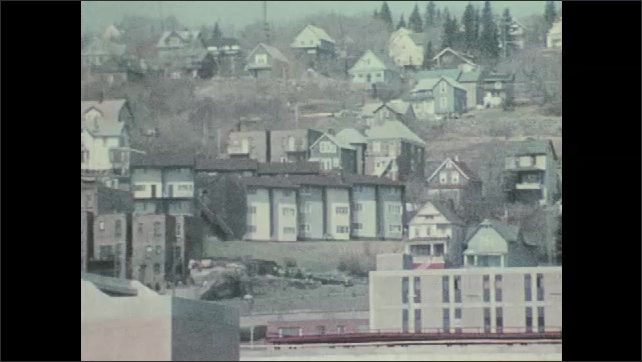 1970s: UNITED STATES: View across city. Buildings in town settlement. Cars in busy city street.