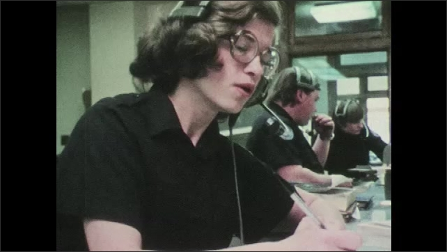 1970s: UNITED STATES: Control room operator takes details of call. Lady writes notes at desk. Lady speaks into headset.