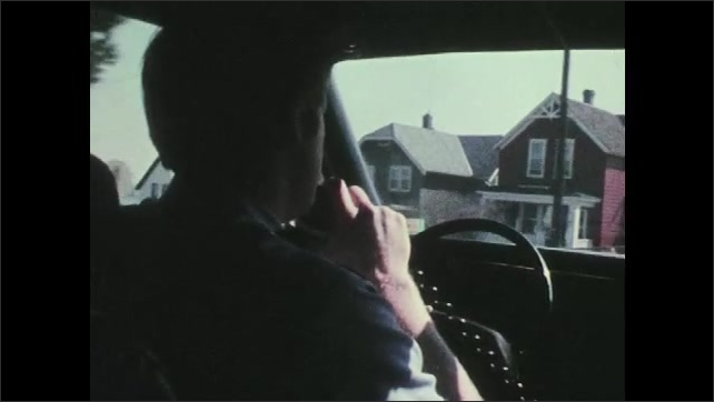 1970s: UNITED STATES: police car drives along street. Police man in car answers radio. Emergency call operator relays information