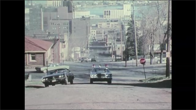 1970s: UNITED STATES: police car drives along street. Police car drives up steep street in city.