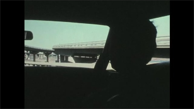 1970s: UNITED STATES: passenger sits in car. View of freeway through car window. Police officers sit in moving car.