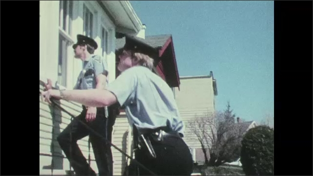 1970s: UNITED STATES: police officers visit house. Police officer looks up at house. Officers climb steps to house. Police officers enter house