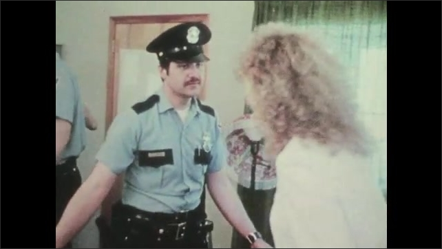 1970s: UNITED STATES: police officers attend to domestic disturbance between man and woman in house. Officer talks to lady