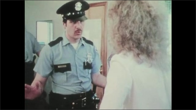 1970s: UNITED STATES: police officers split up arguing couple. Photograph of police officer and angry lady.